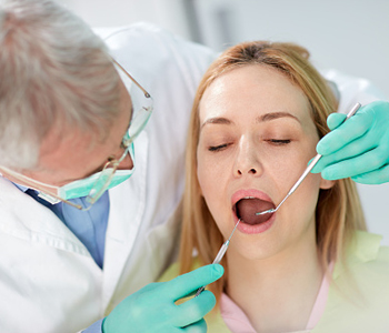 Dentist checking female patient's mouth