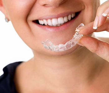 A Woman holding invisalign braces