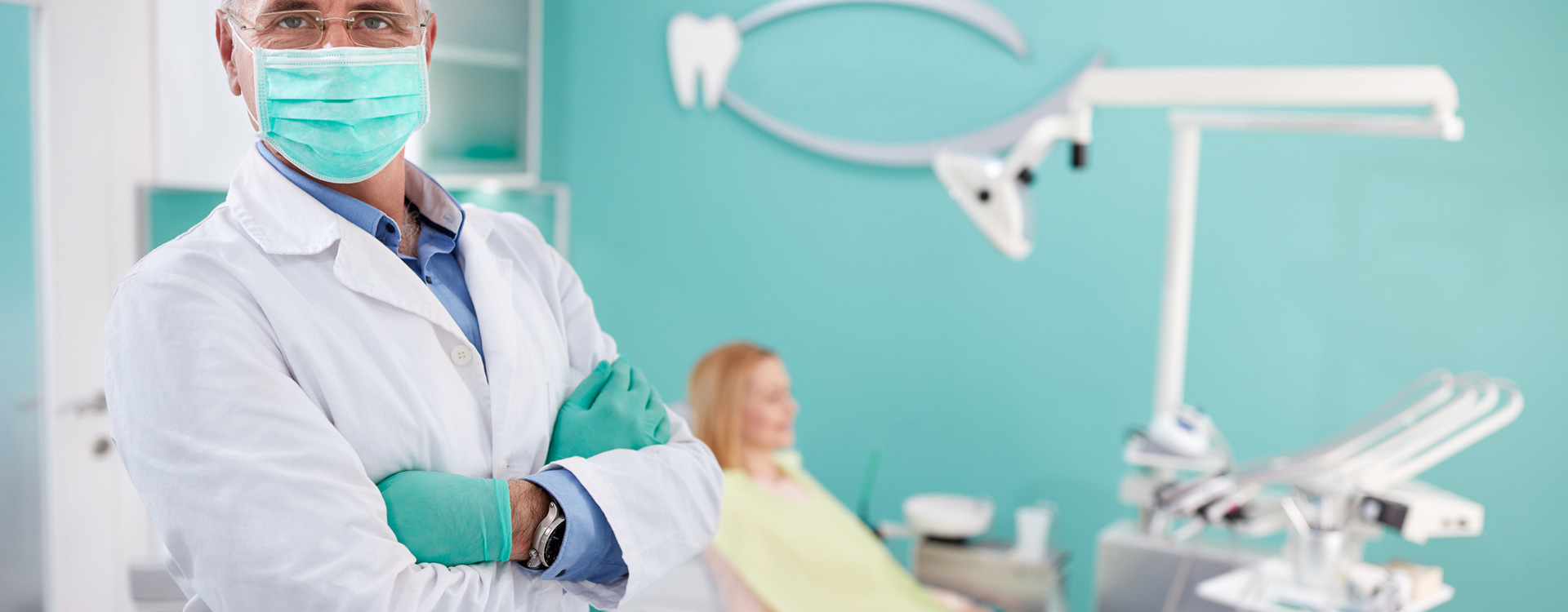 Doctor focusing to camera at dental office with a patient in background